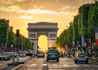 The sun sets above the Arc De Triomphe.