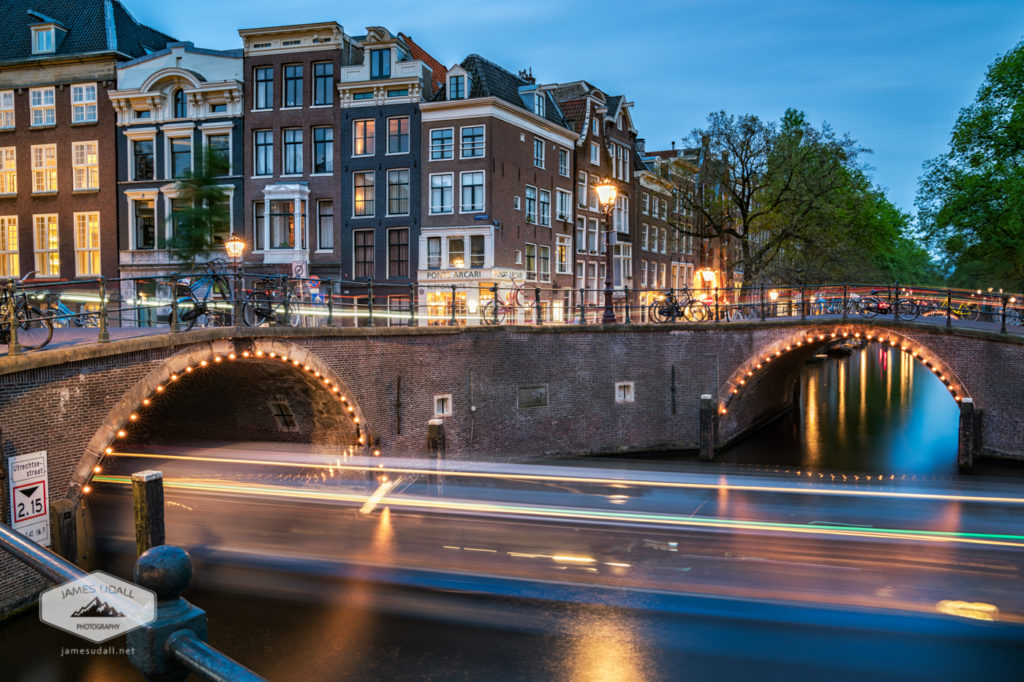 A boat cruises along the Herengracht, a canal in Amsterdam.